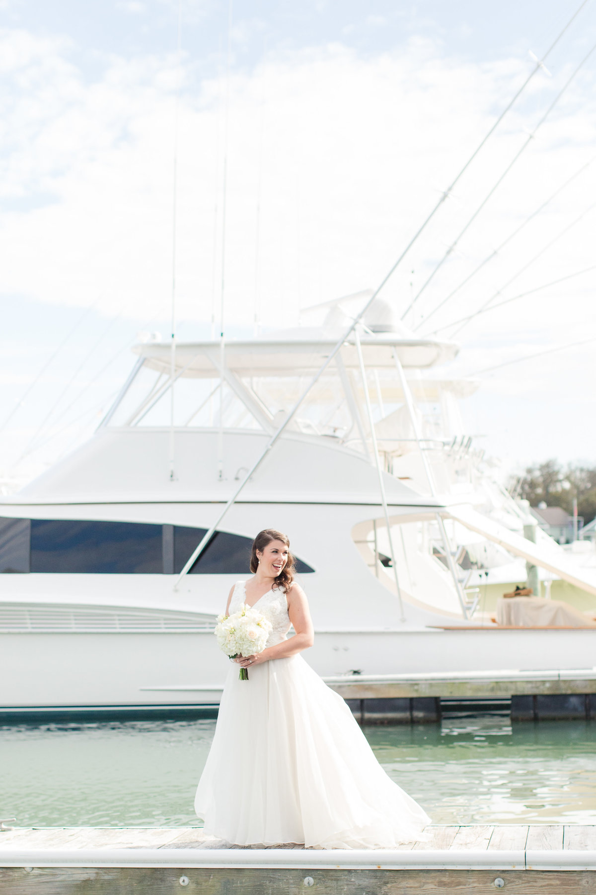 Smiling bride in front of a white yacht at The Water Table