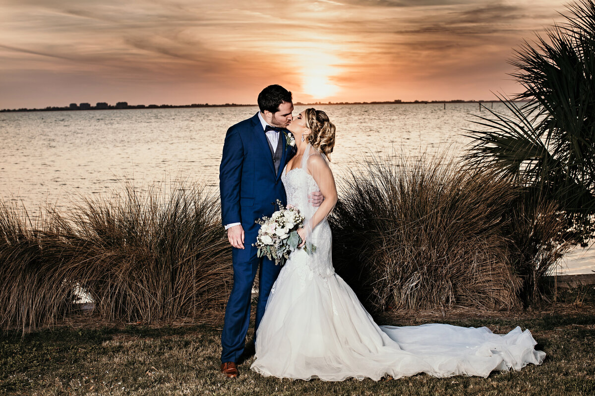 An image of the bride and groom romantically kissing as they stand embracing in front of some lovely plants with the open water and setting sun behind them by Garry & Stacy Photography Co - Tampa FL wedding photographer