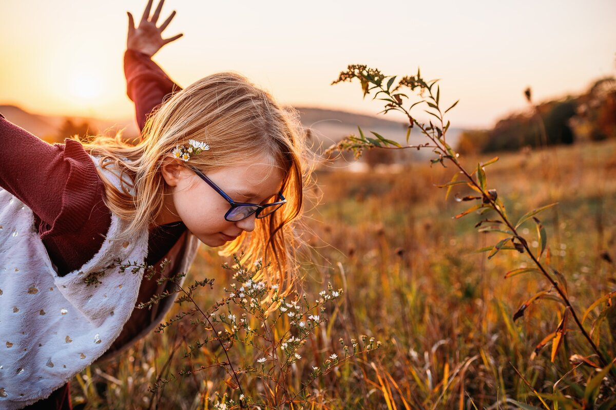 Child with long hair and glasses leaning forward to smell flower, arms outstretched behind.