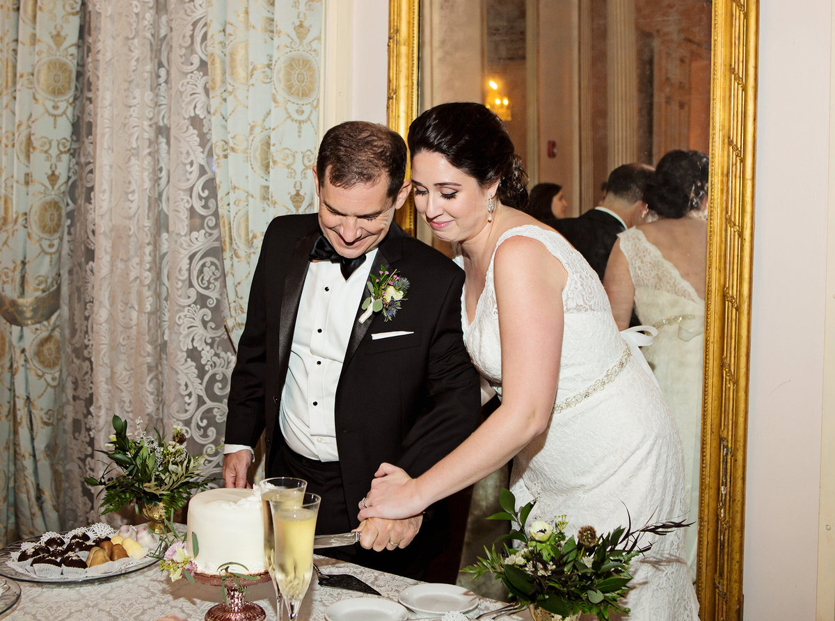 New Orleans wedding couple cutting the cake at their wedding reception at The Columns Hotel