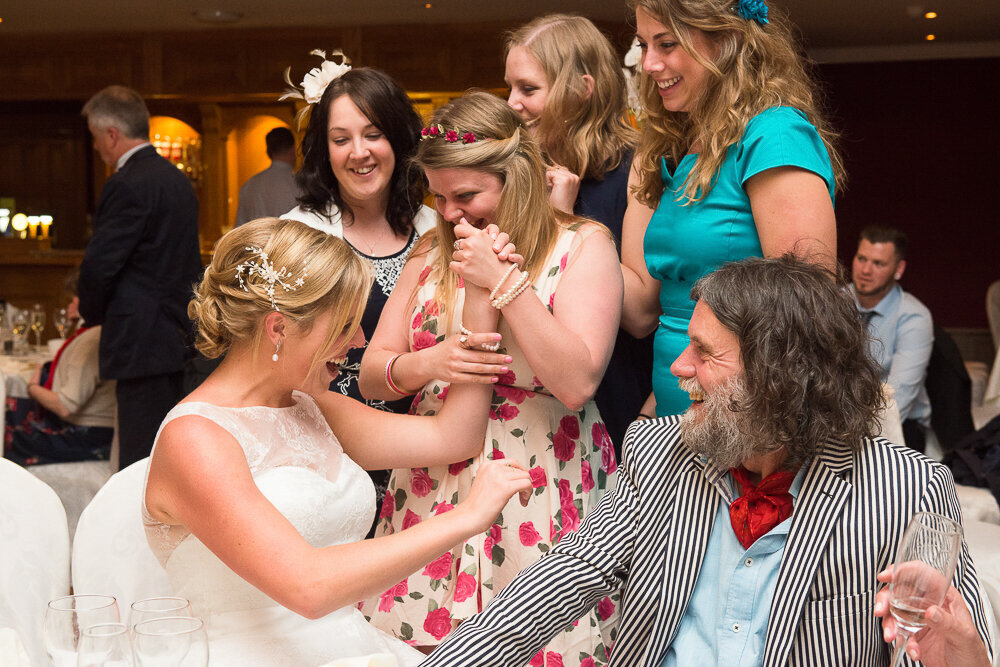 blonde bride sharing a fun time with her friends at her wedding reception in the Dingle Skellig Hotel while sitting beside a man with a black and white striped jacket and red cravat