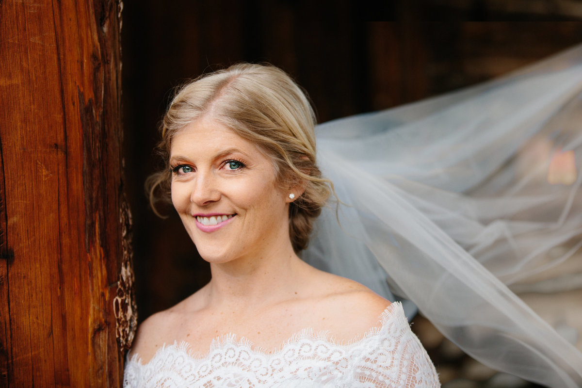 A bride next to a pole smiles.