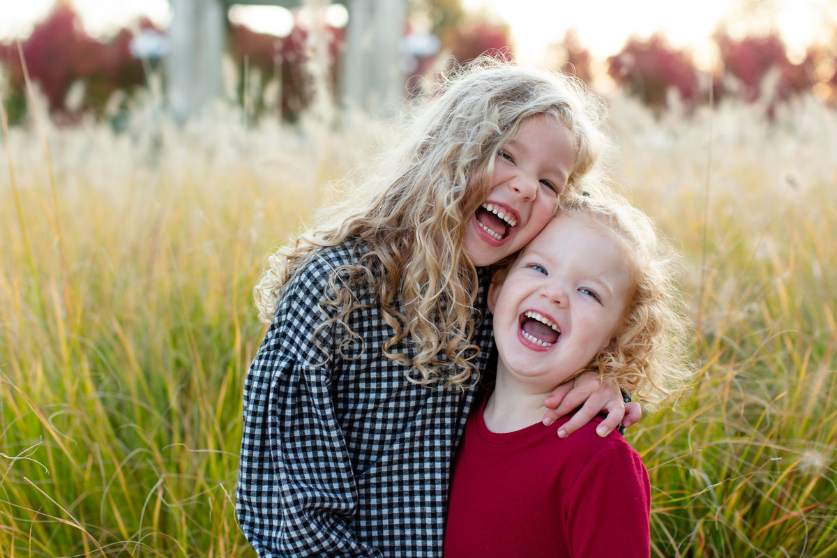 Fall Sunset Family Session 2 sisters laughing by tall grass at Pagoda Circle in Forest Park in St. Louis by Amy Britton Photography Photographer  in St. Louis