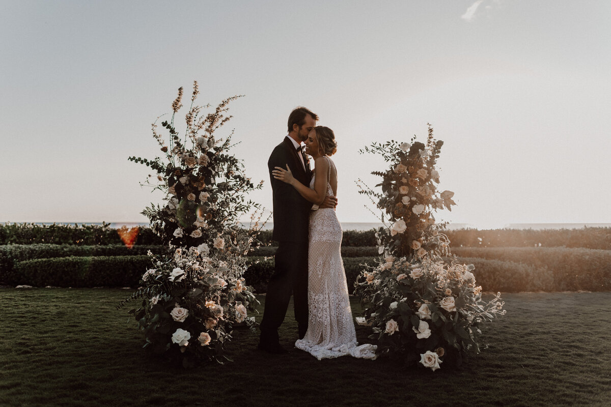 Over-the-top-floral-wedding-installation-with-bride-and-groom-kissing-in-front