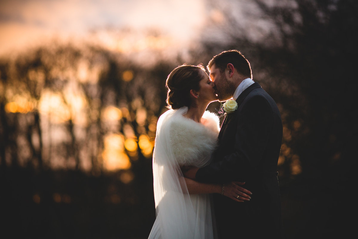 a bride and groom kissing at sunset