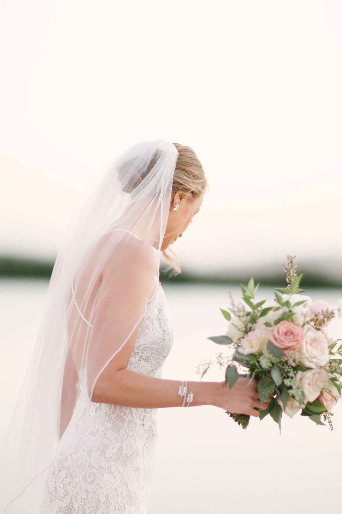 Bride walks along lake at Firestone Vineyard