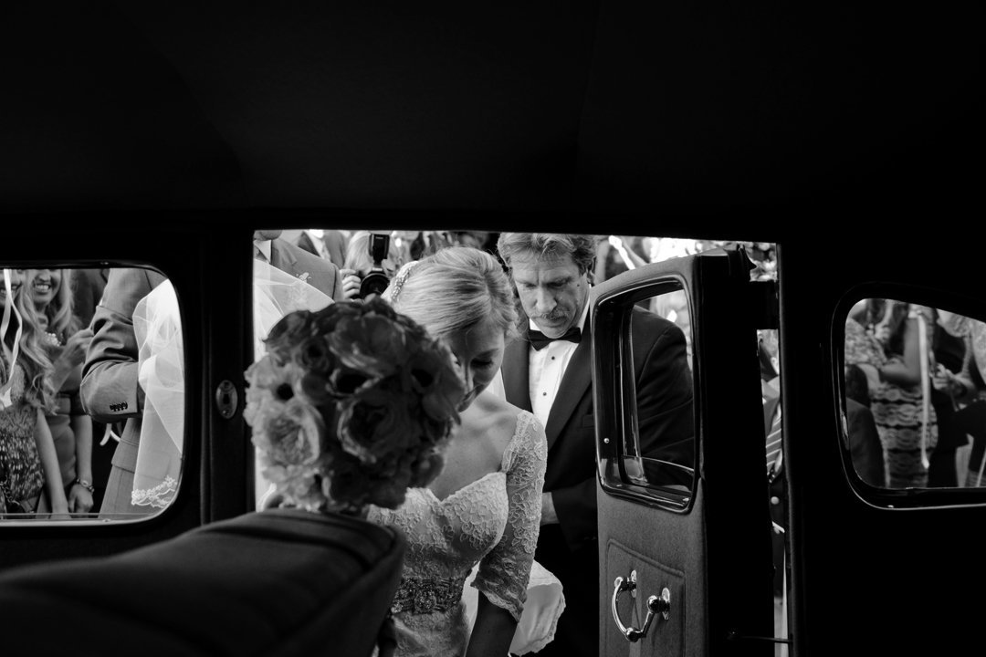 Bride getting into classic car after wedding ceremony, Washington DC Fine Art Wedding Photography by Erin Tetterton