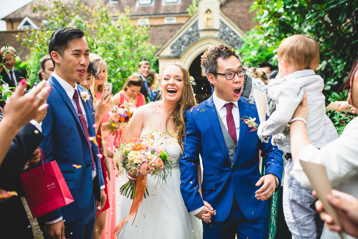 baby throwing confetti and bride and groom in blue suit boho wedding