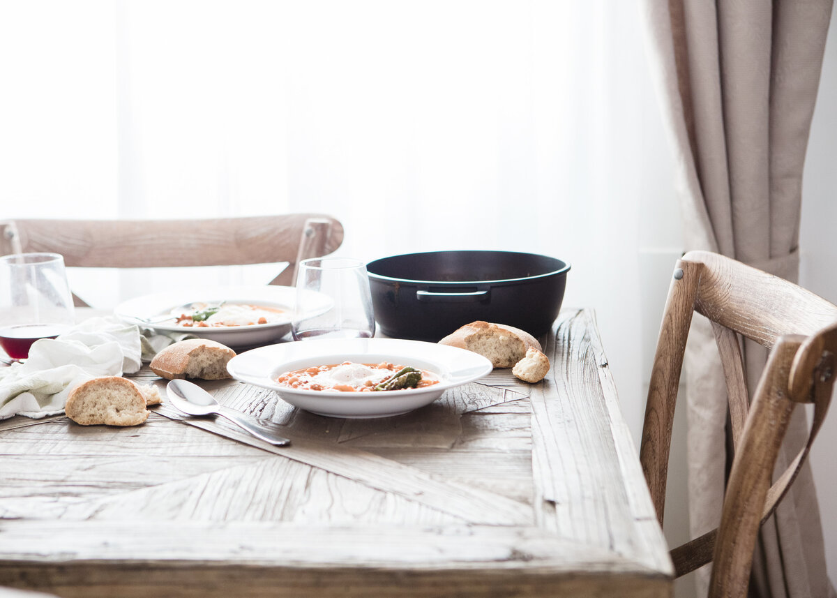 A close up of a dinner with bread on a parquet table in a rustic interior design.
