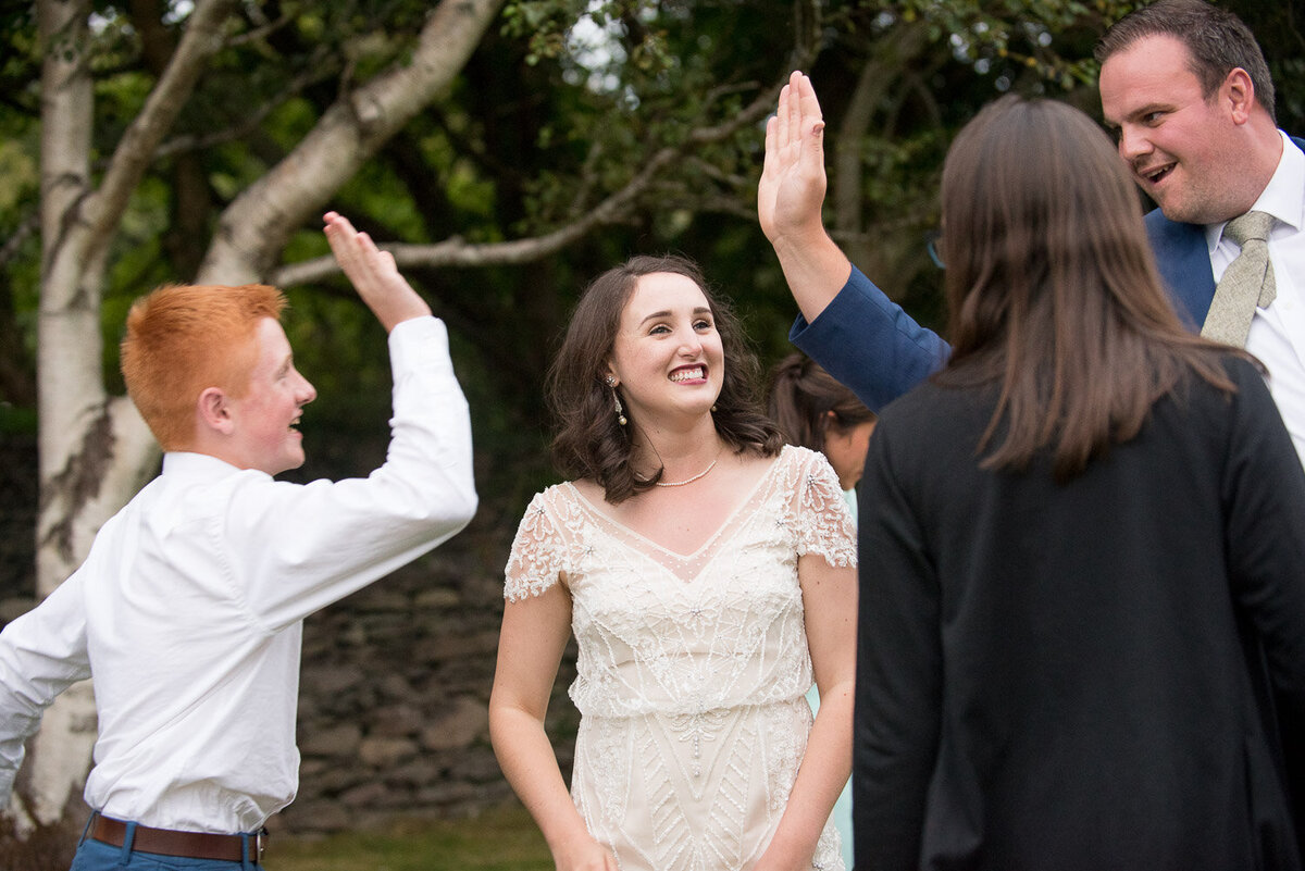 bride in vintage wedding dress watching two wedding guests doing a high five at Castlecove House