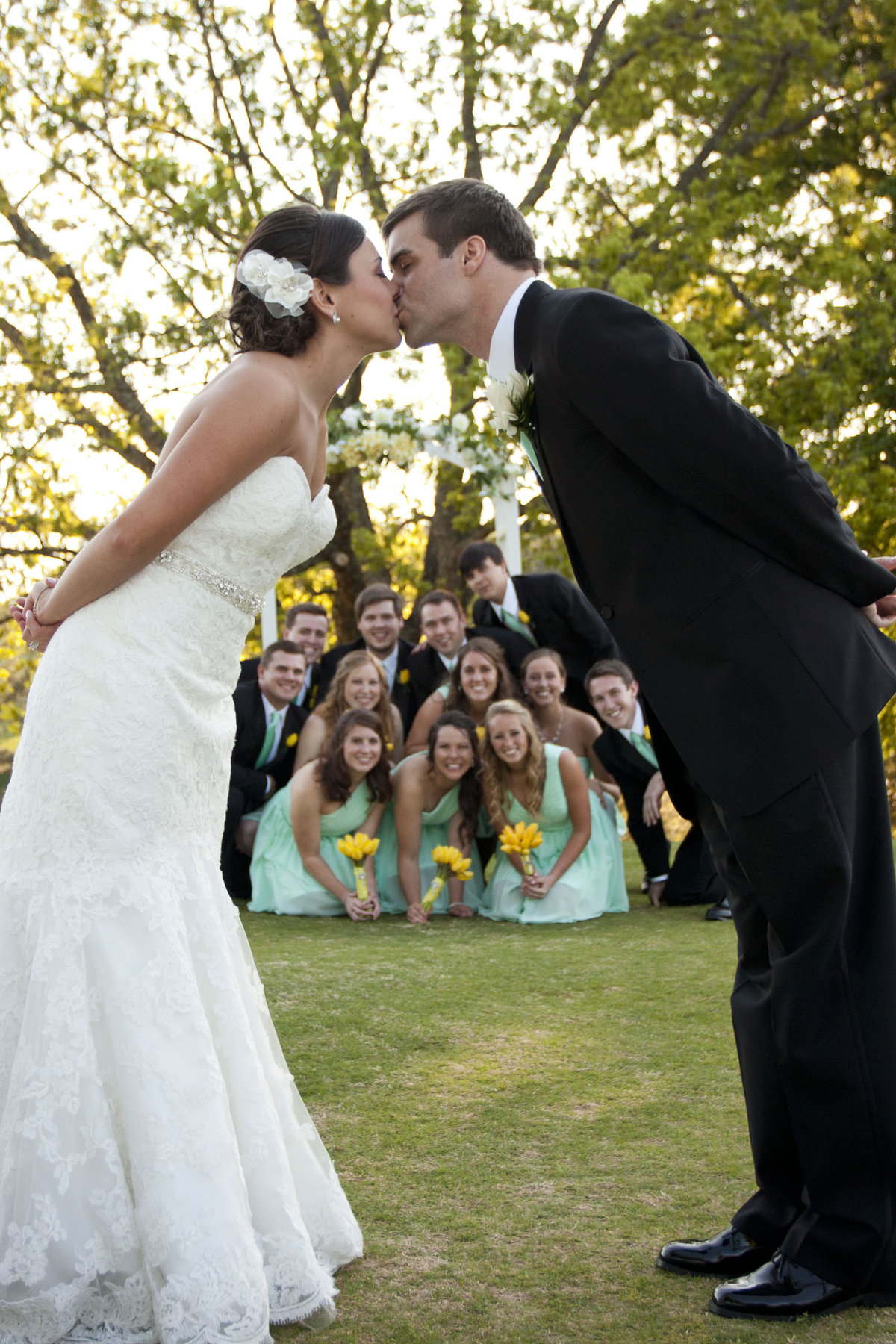Bride and Groom kiss bridal party in background in teal dresses