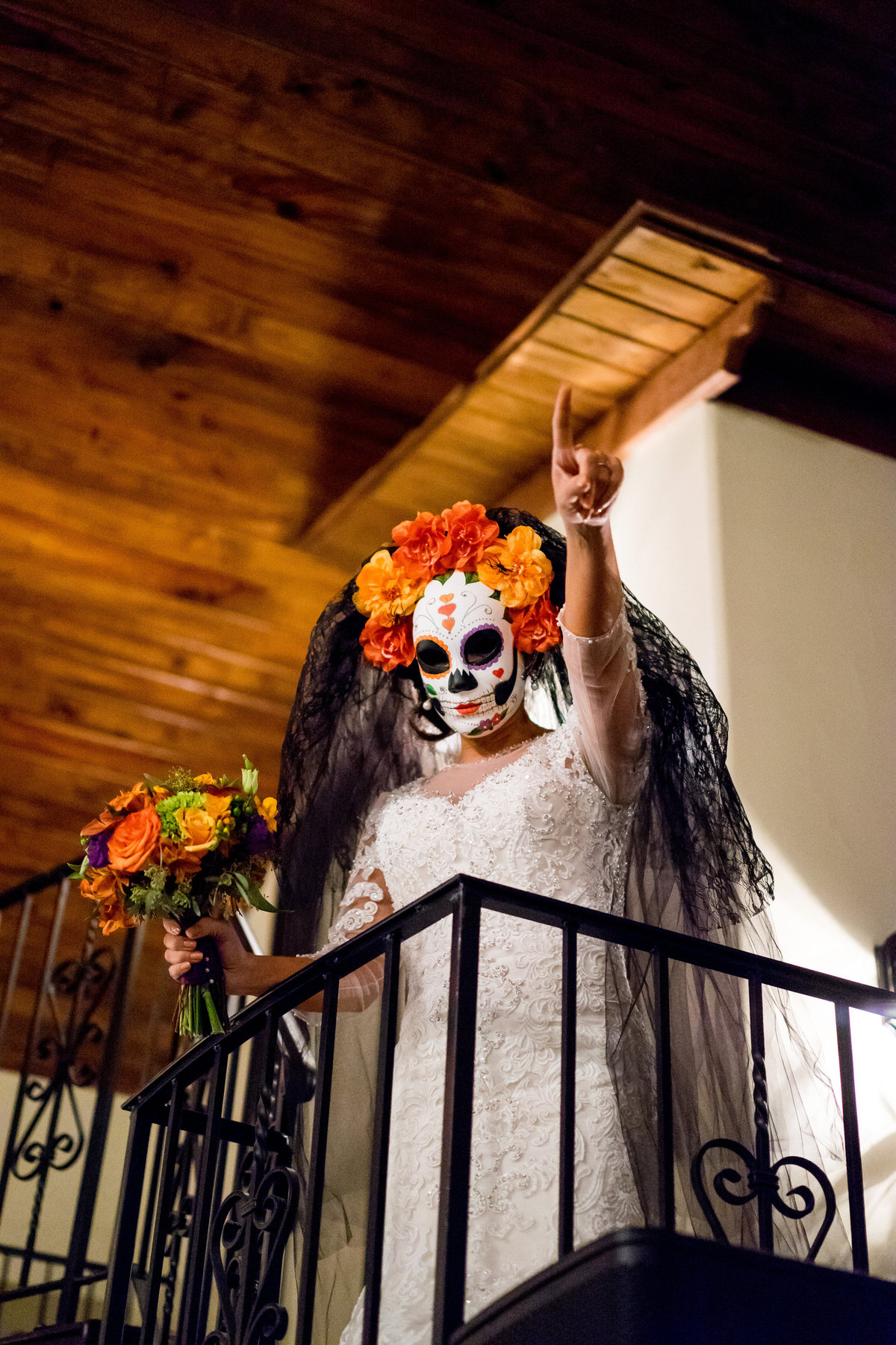 Bride wearing a dia de los muertos mask during reception at Halloween wedding to honor day of the dead at Marquardt Ranch