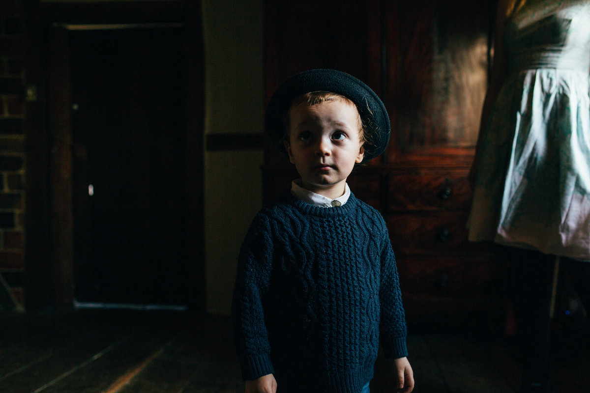 Natural photo of toddler boy wearing a hat at home in norfolk in the shadows