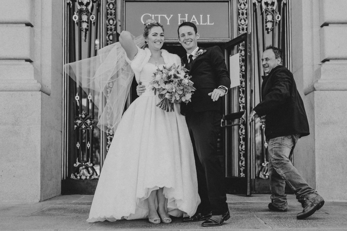 bride and groom in front of san francisco city hall veil caught in wind