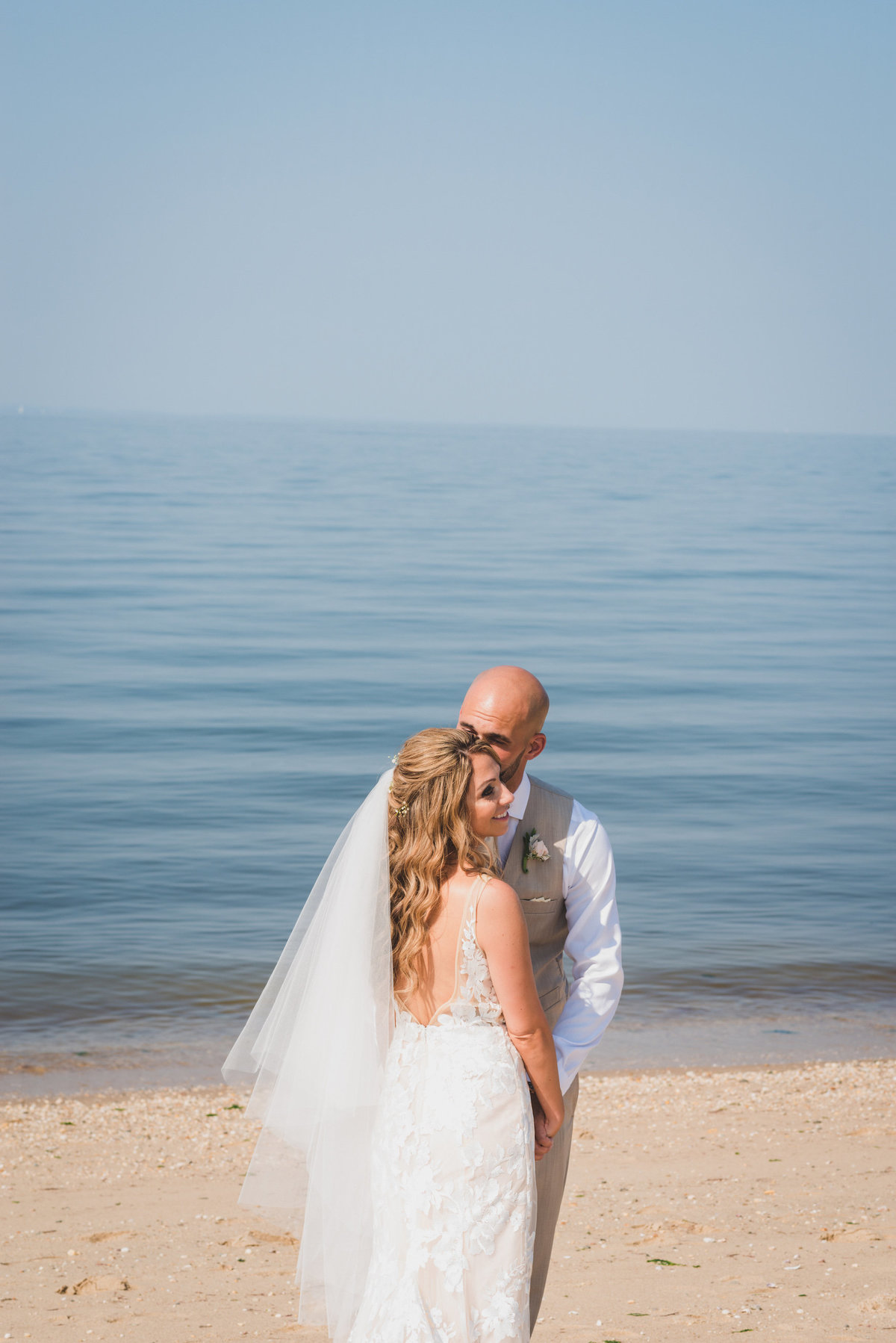 photo of groom and bride on the beach near the water from wedding at Pavilion at Sunken Meadow
