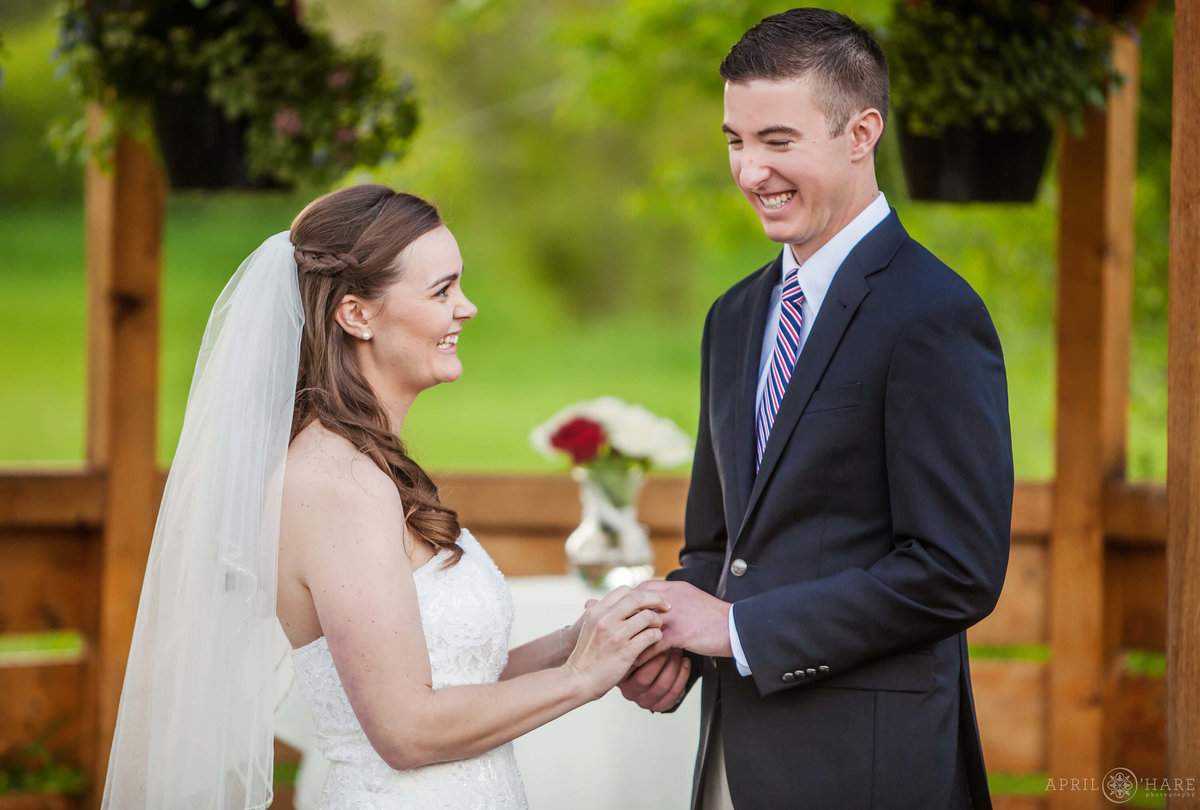 Bride and groom laugh with each other during wedding ceremony at Denver Botanic Gardens Chatfield Farms