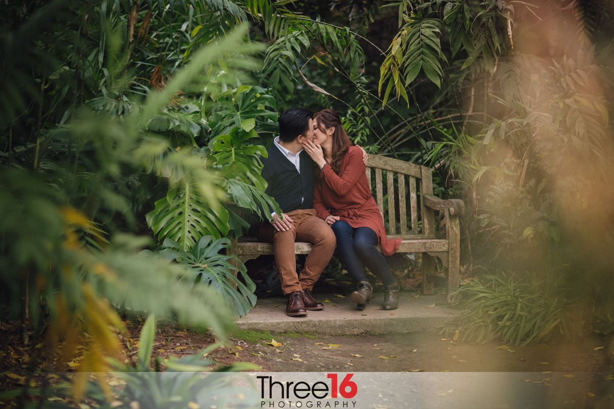 Young couple share a quiet kiss during their engagement photo shoot