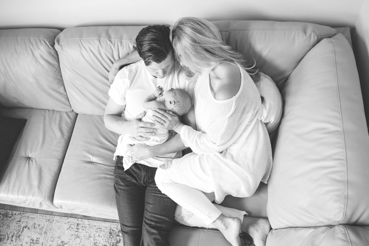parents holding newborn baby son on couch {Oakville Lifestyle Photographer}