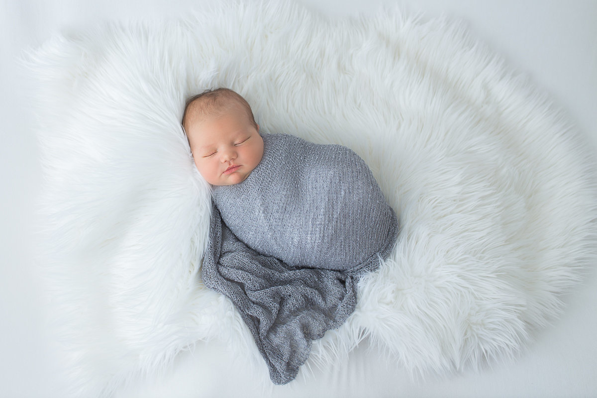 baby boy in grey swaddle sleeping on white fur {Oakville Newborn Photographer}