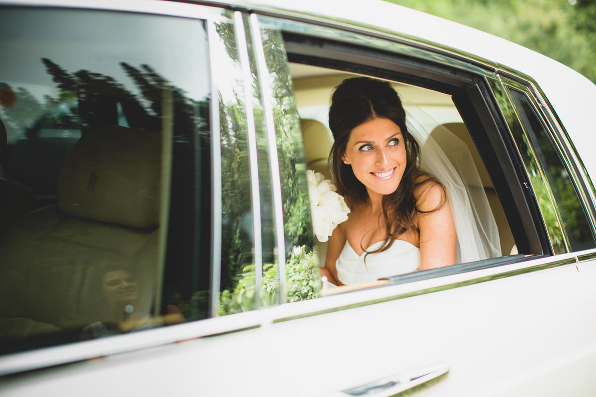 greek wedding photography of a bride arriving at the church in a white rolls royce phantom