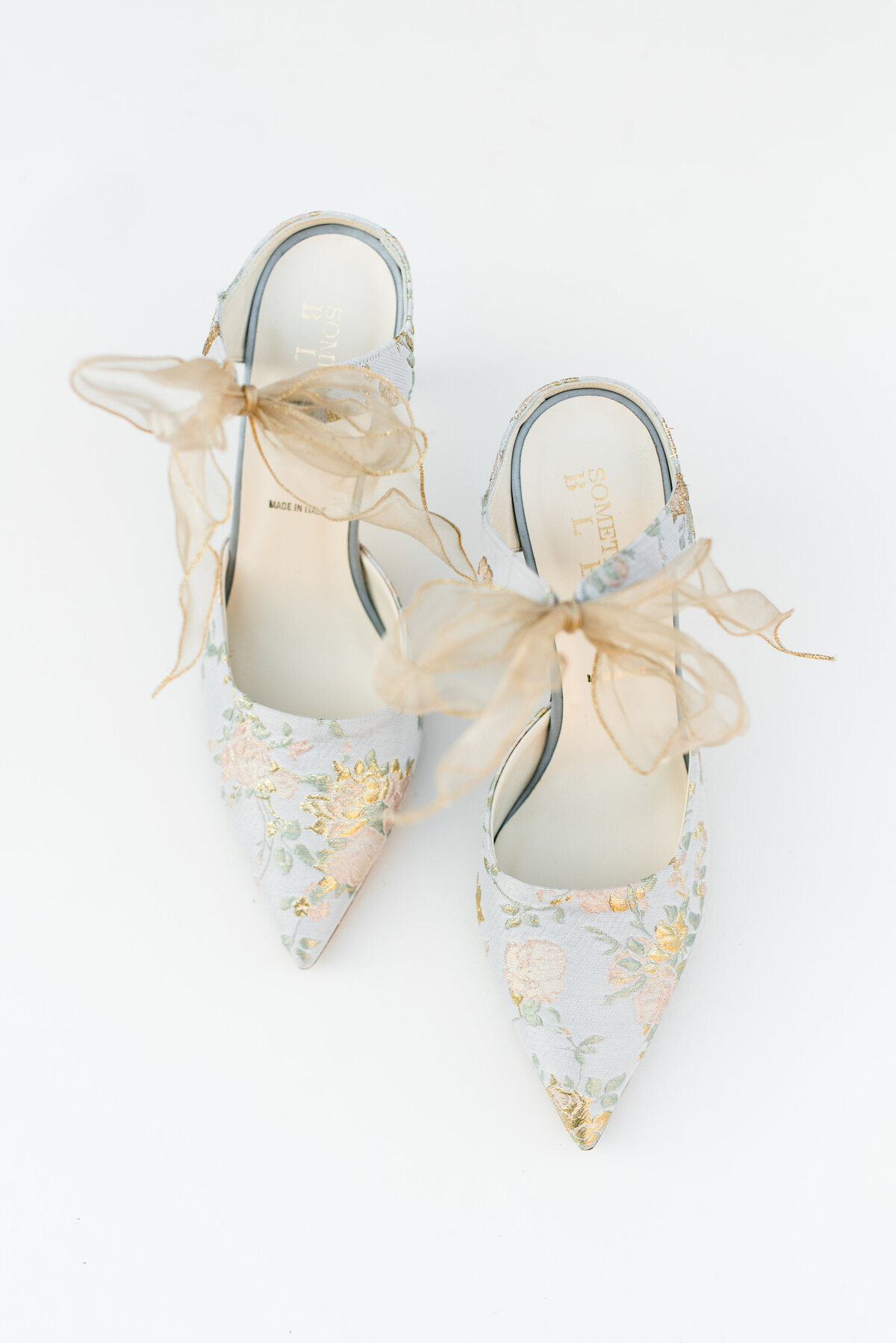 A pair of Something Bleu wedding shoes sits on a white backdrop
