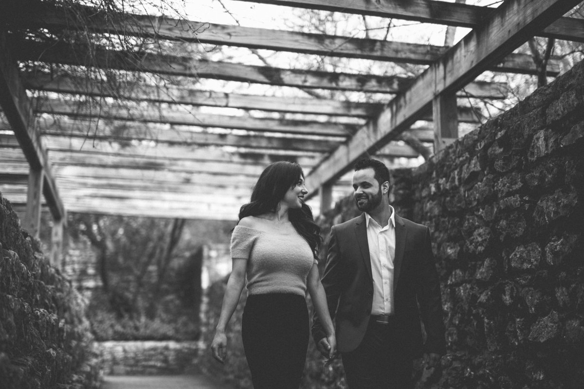 Black and white photo of couple walking under covered garden on their engagement session at the San Antonio Botanical Garden.