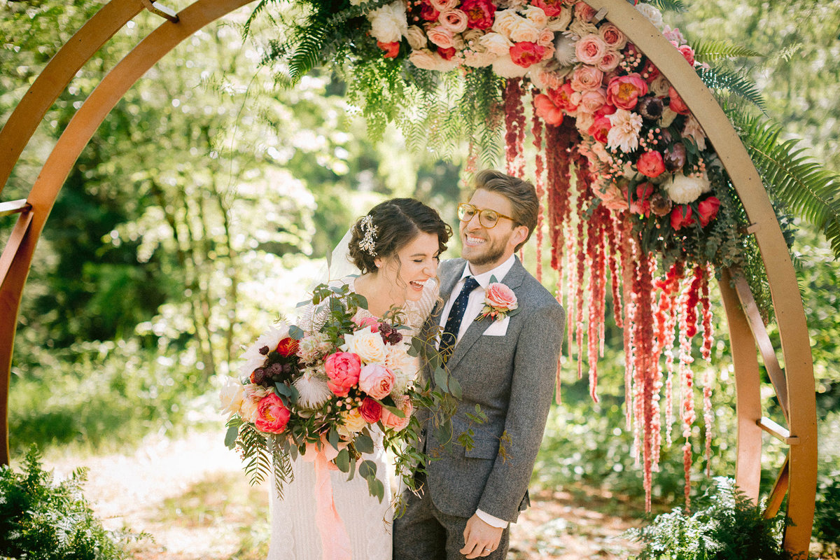 bride and groom laughing at floral arch altar wedding