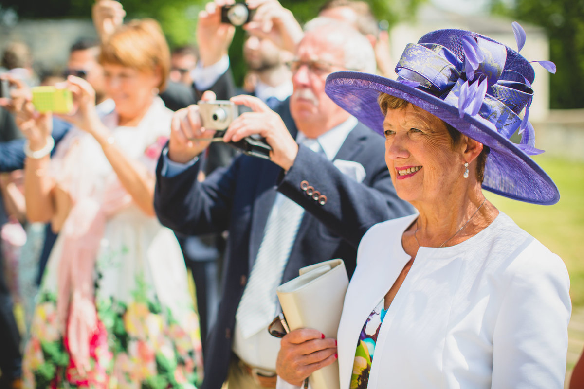 mother of the bride smiling at wedding wearing lilac hat