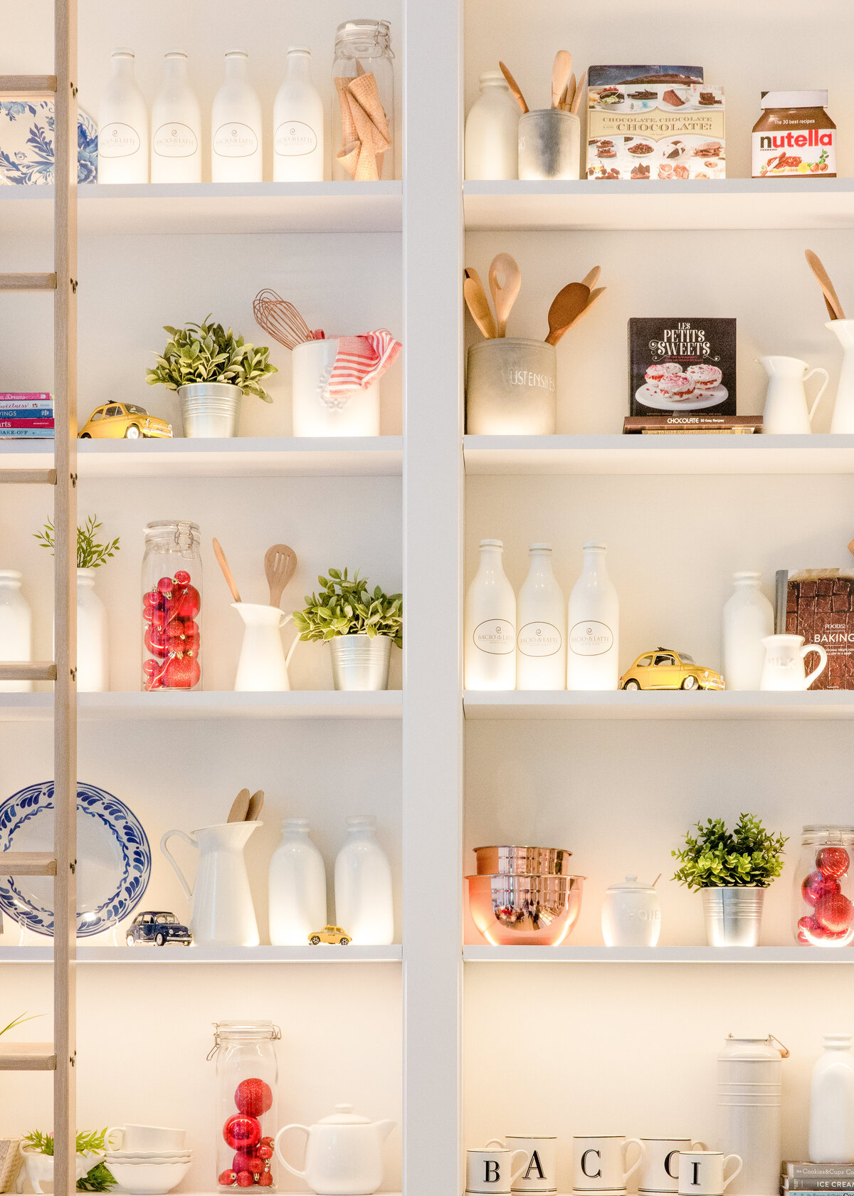 A well presented pantry is organised with white ceramic bottles, a ladder to reach higher larder shelves and red tomatoes.