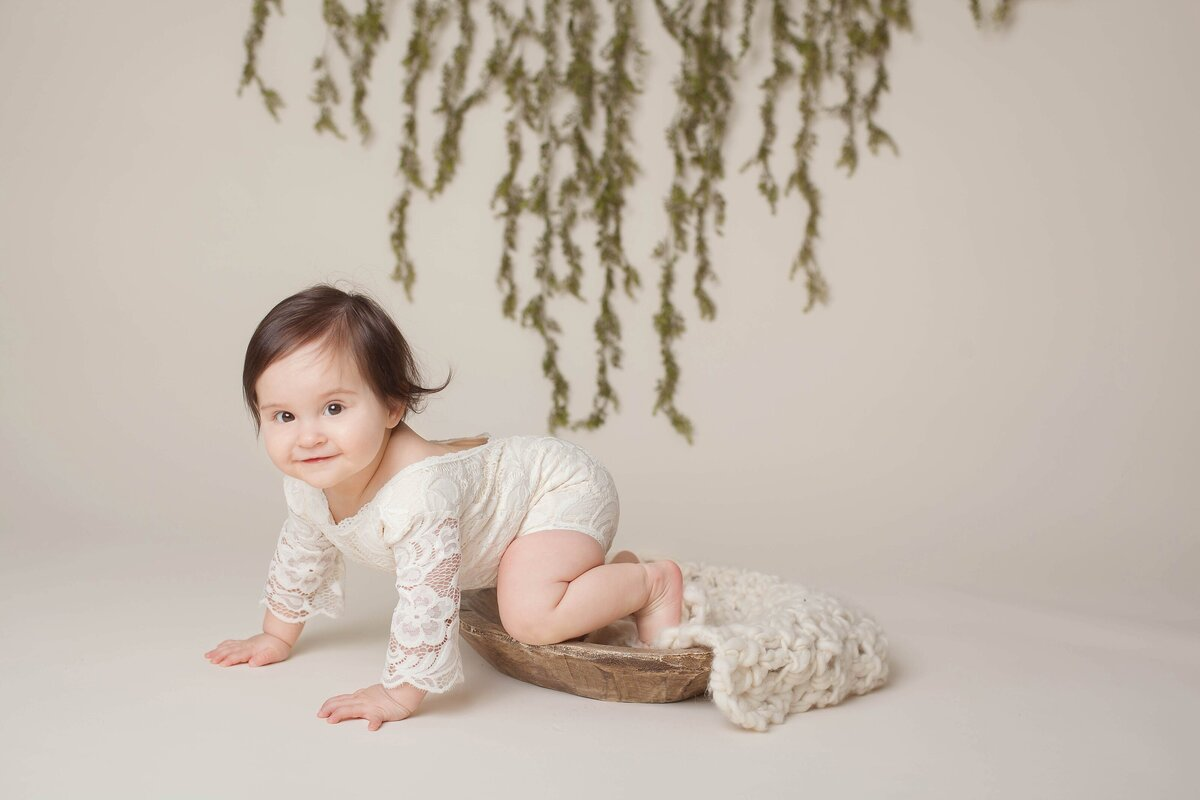 milestone baby  1 year old session crawling white outfit greenery