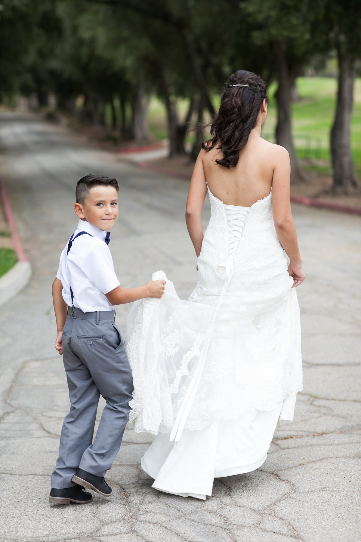 candid photo of son helping  mom by holding wedding dress