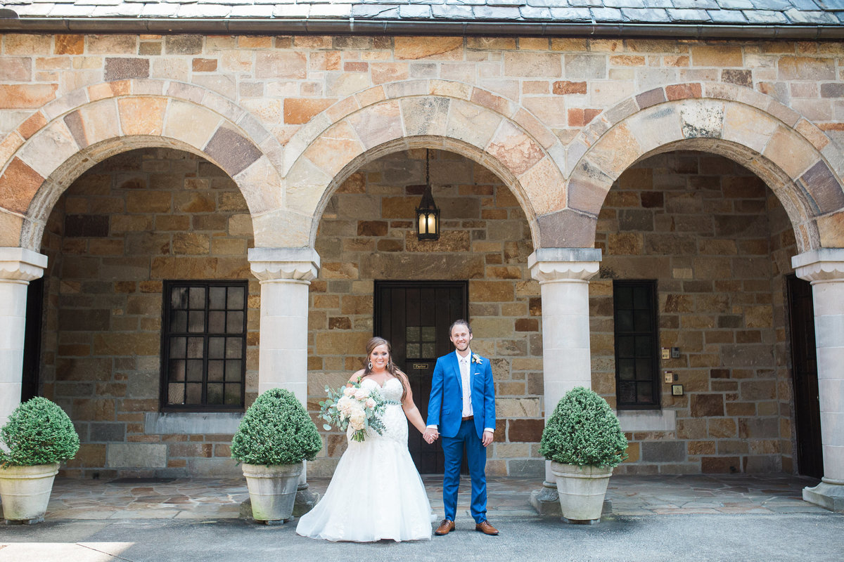 Wedding Photographer, bride and groom standing in front building columns
