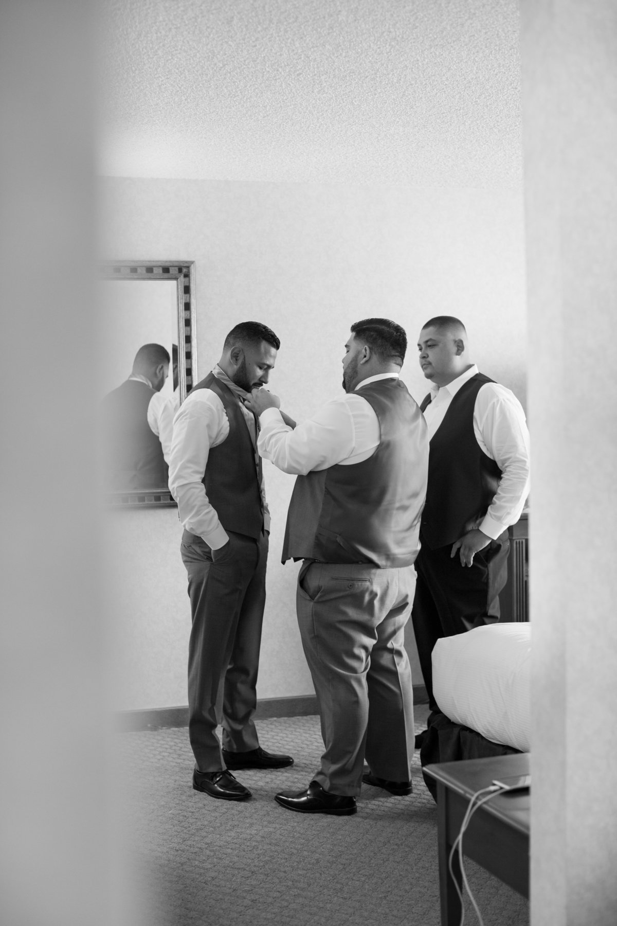 groomsmen lend a hand out and prep tie before wedding in los angeles california