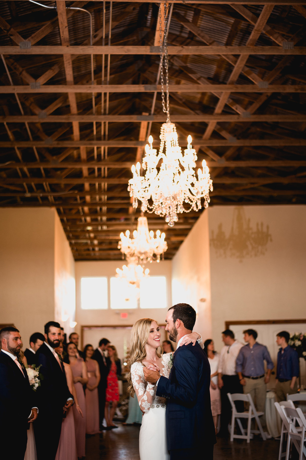 Bride and groom first dance under chandeliers at Seven Hill Farm
