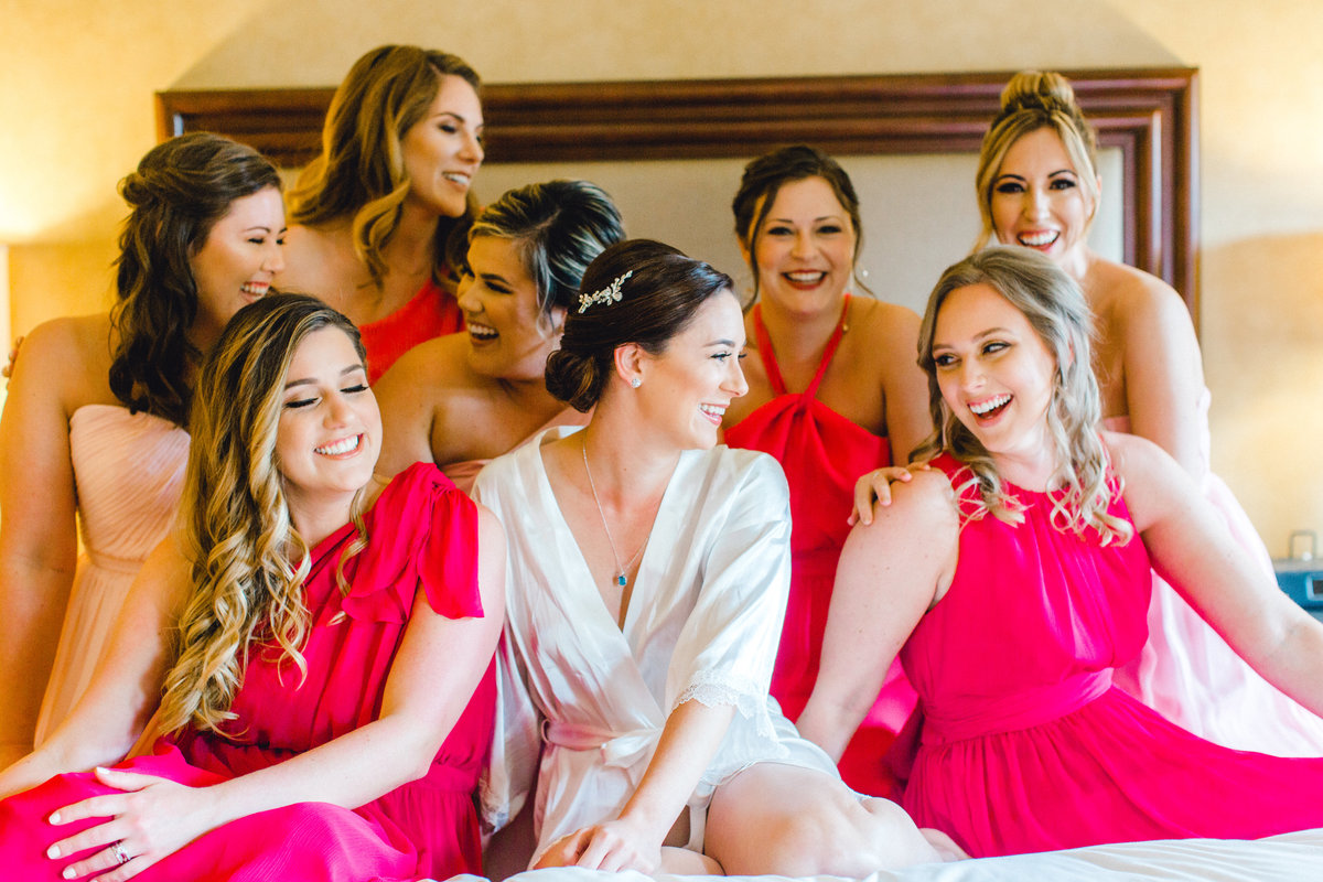 Bride and her bridesmaids laughing on the bed ebfore getting ready at Vintners Inn in Santa Rosa California