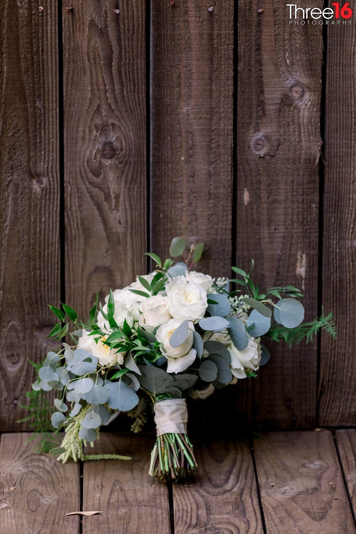 Brides bouquet resting up against a wooden fence