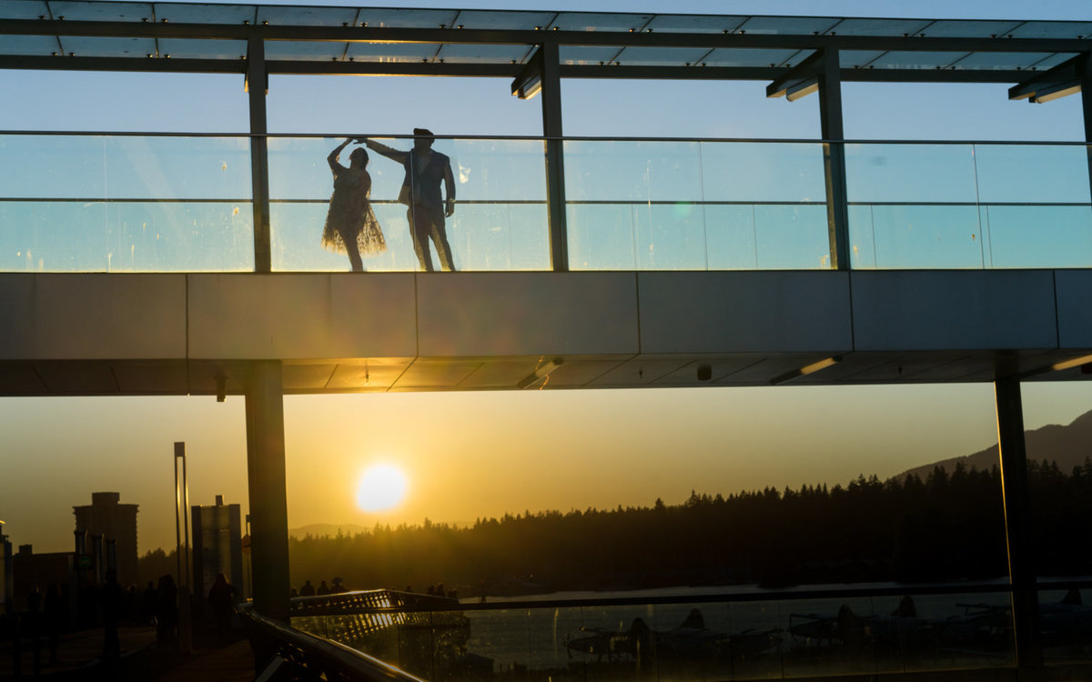 Vancouver downtown engagement photo during sunset as couple dances.