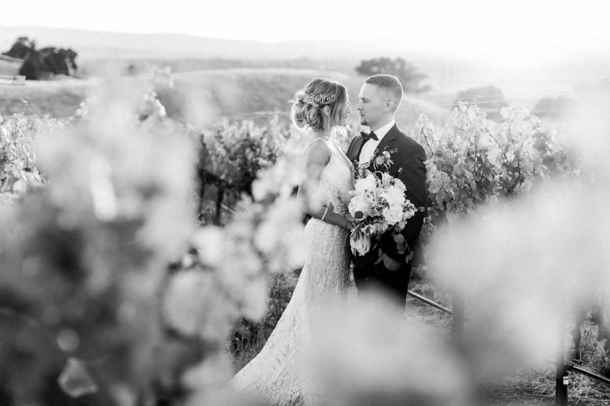 Bride and groom gazing into each others eyes in a vineyard