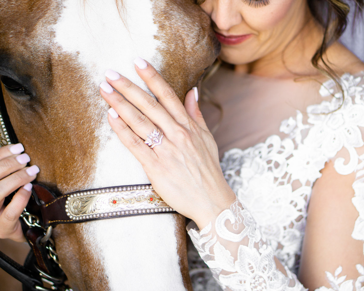 Bride nuzzling horse while showing off her ring  with her hand on his nose