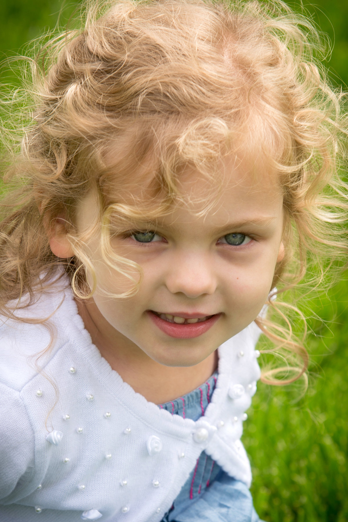 Cute curly haired girl during a family portrait at Lilacia Park in Lombard
