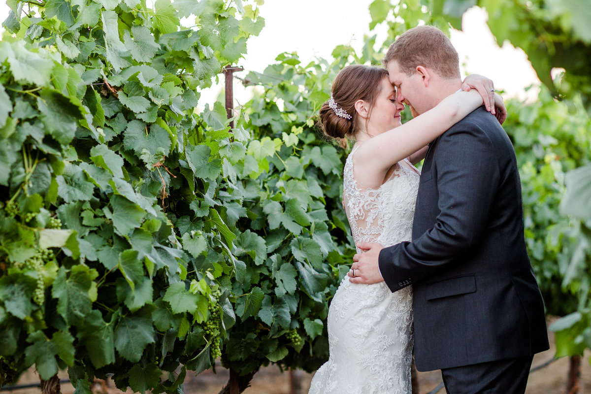Bride and Groom stand hugging forehead to forehead in the vineyard at Palm Event Center in Pleasanton, CA