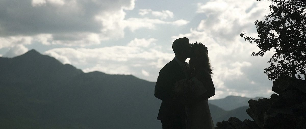 A silhouetted couple embrace in front of a mountain