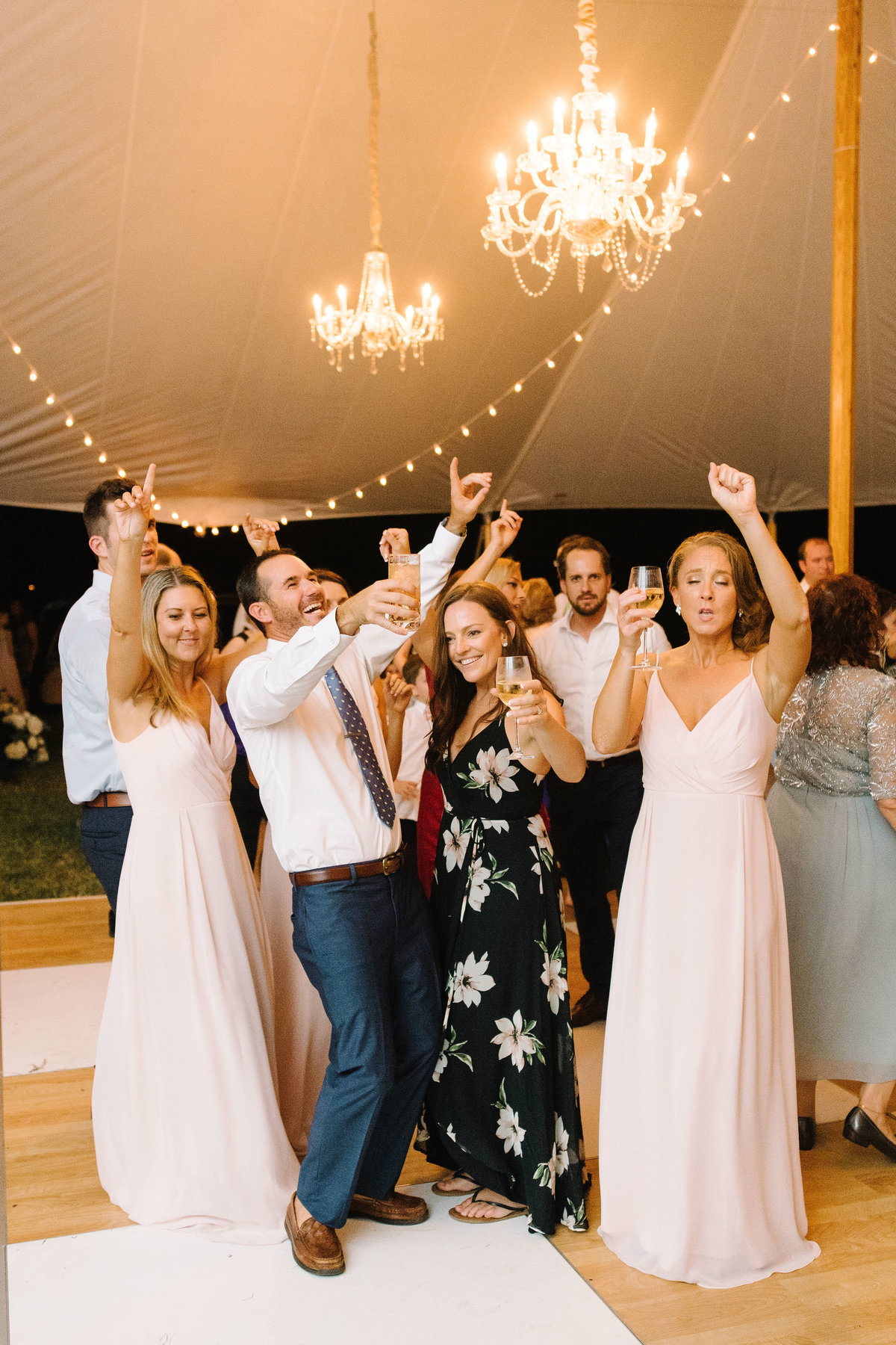 Wedding Guests dancing on Birch Wood and White checkered Dance Floor under Sailcloth Tent with Cafe Lighting and Crystal Chandeliers