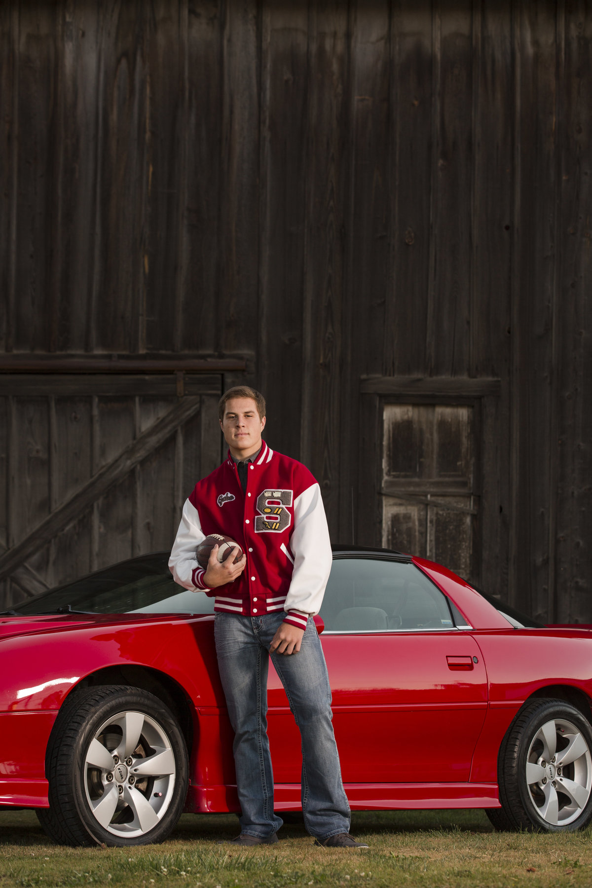 bellingham photographers high school football player senior portrait with car