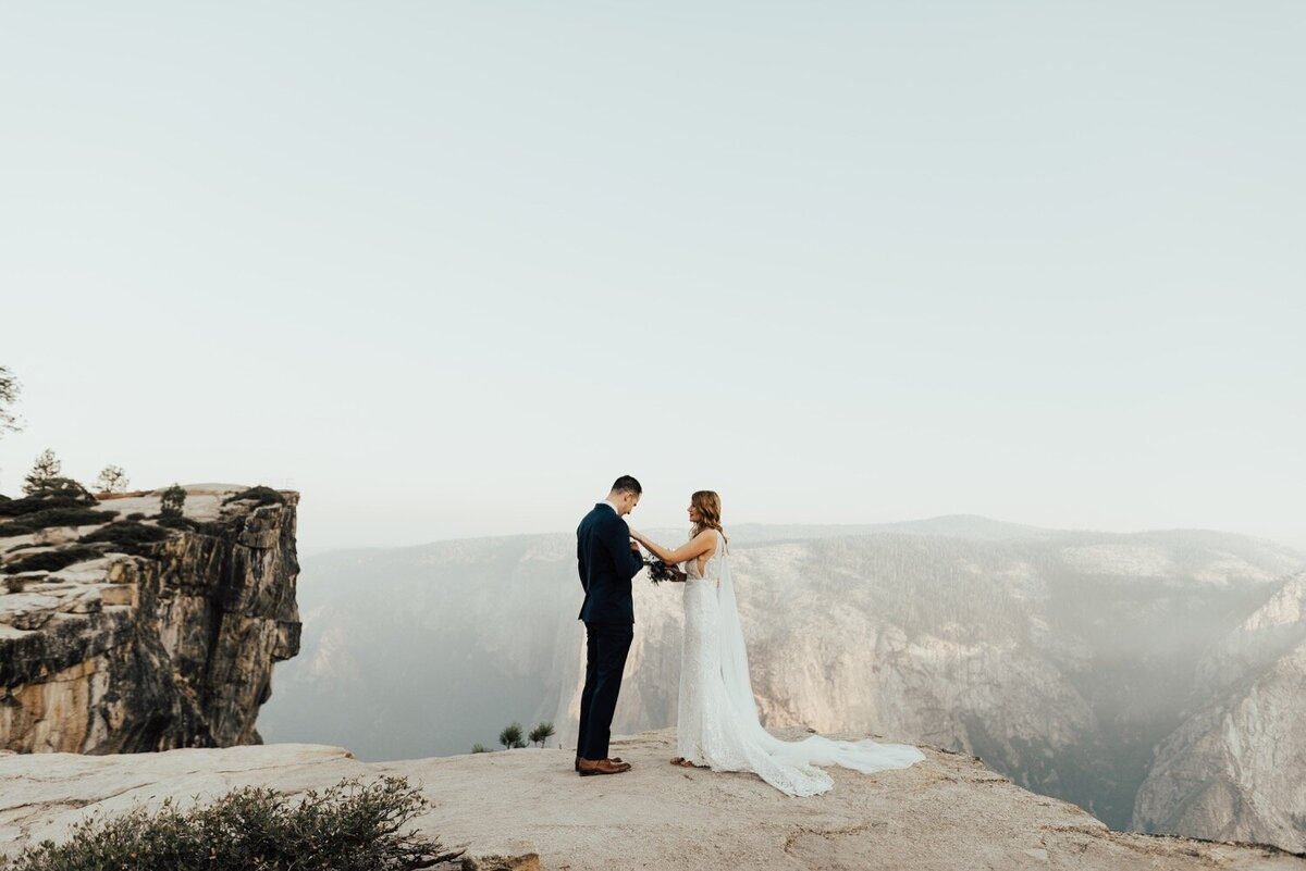 Bride and groom standing on a mountain ledge for their elopement