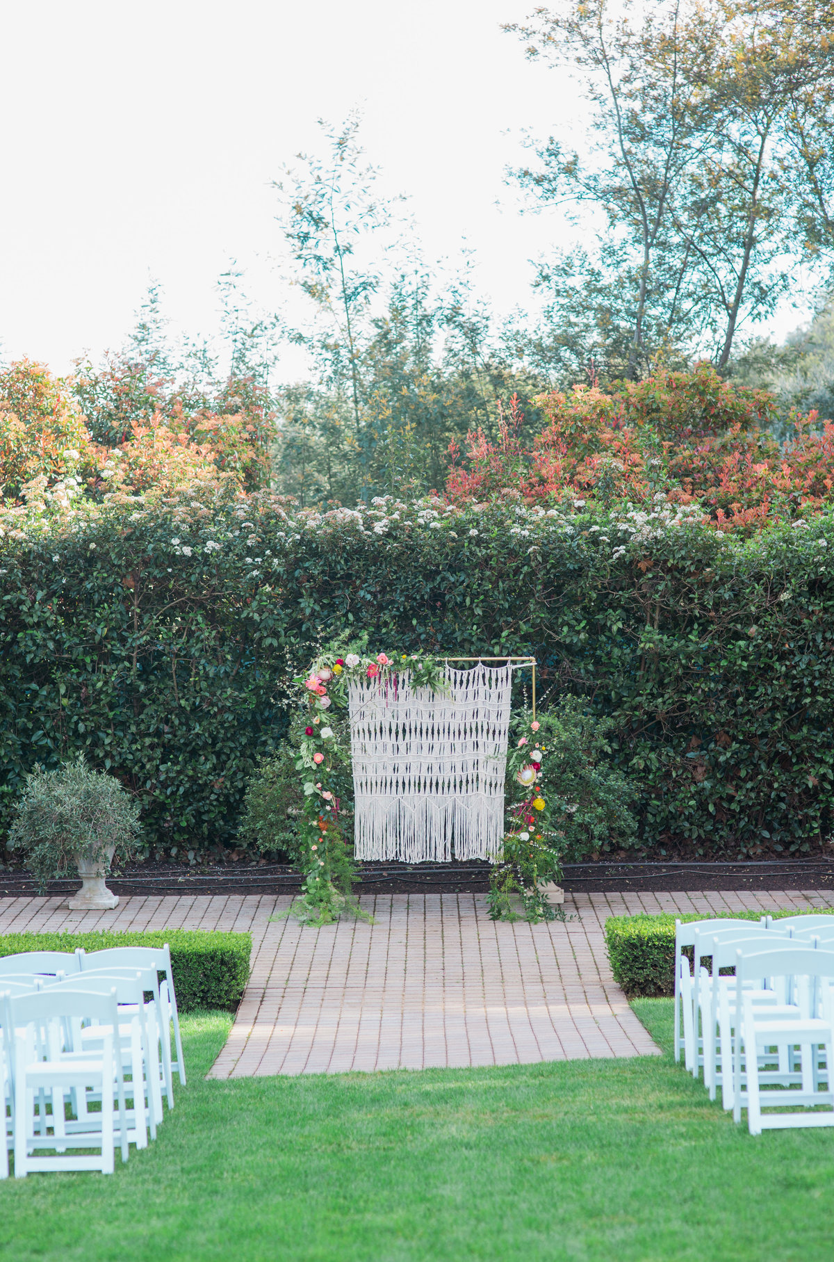 Wide view of ceremony site with boho floral wall at Madrona Manor in Healdsburg California