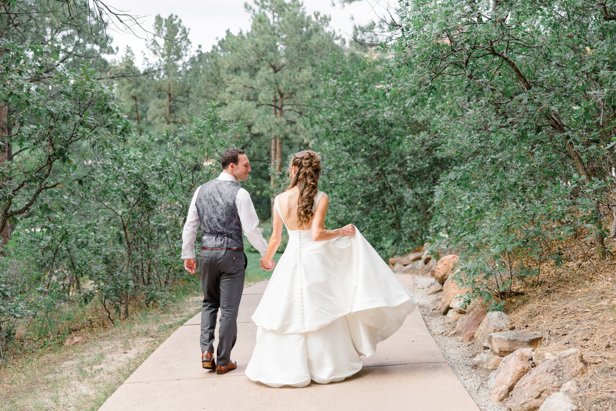Bride and groom walking down path at Castle Pines Golf Club wedding