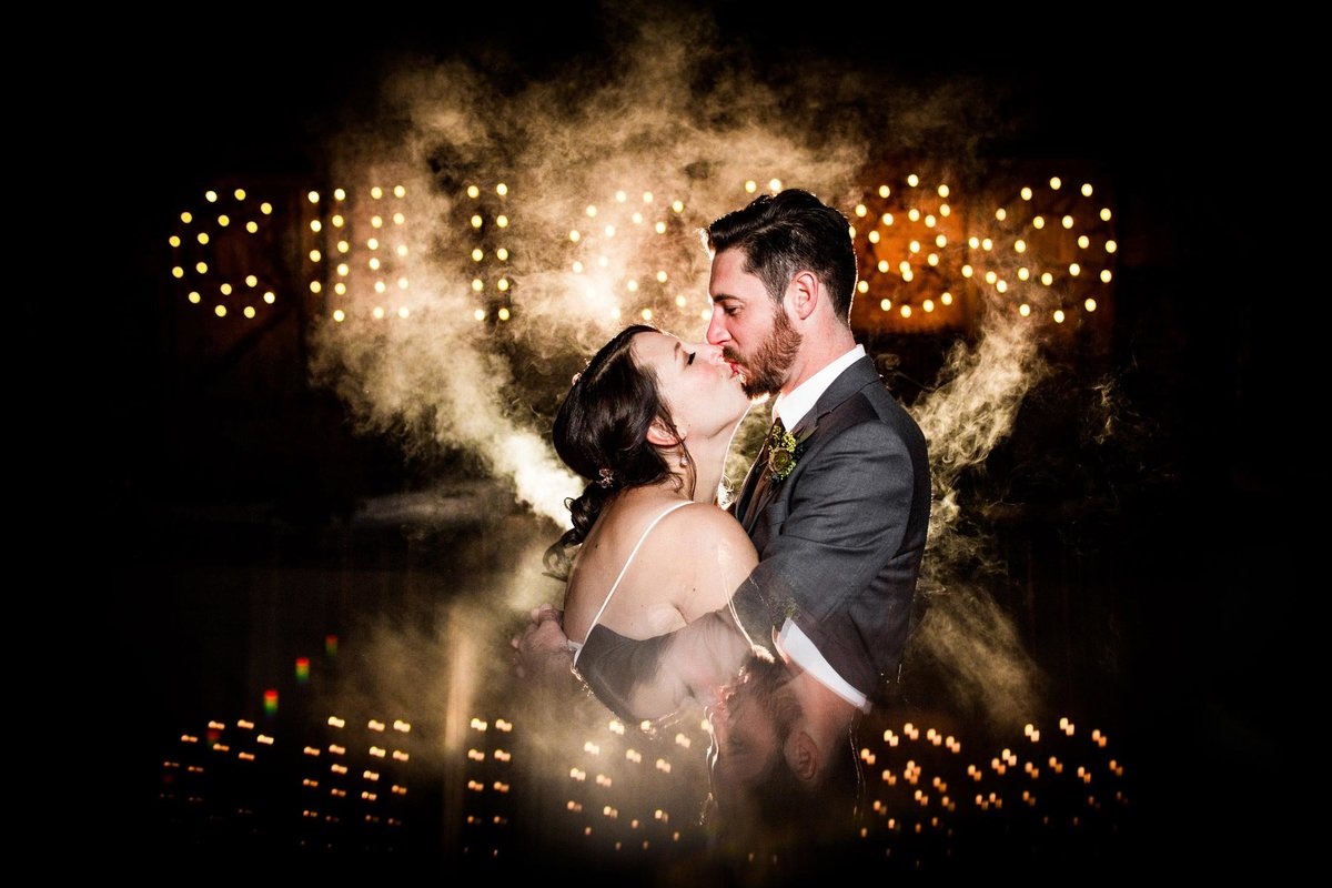 A couple kisses and is reflected in a Chicago sign at their Salvage One wedding.