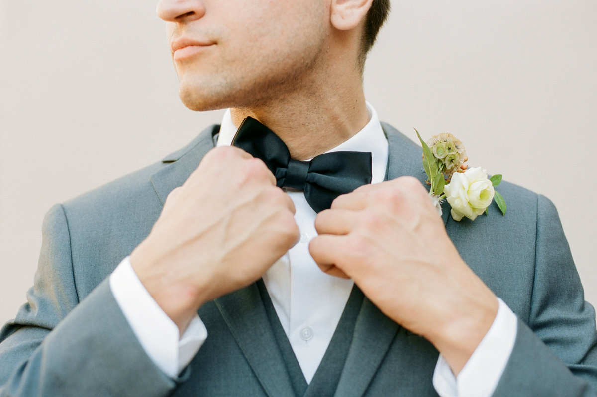 groom in grey suit adjusting black bow tie