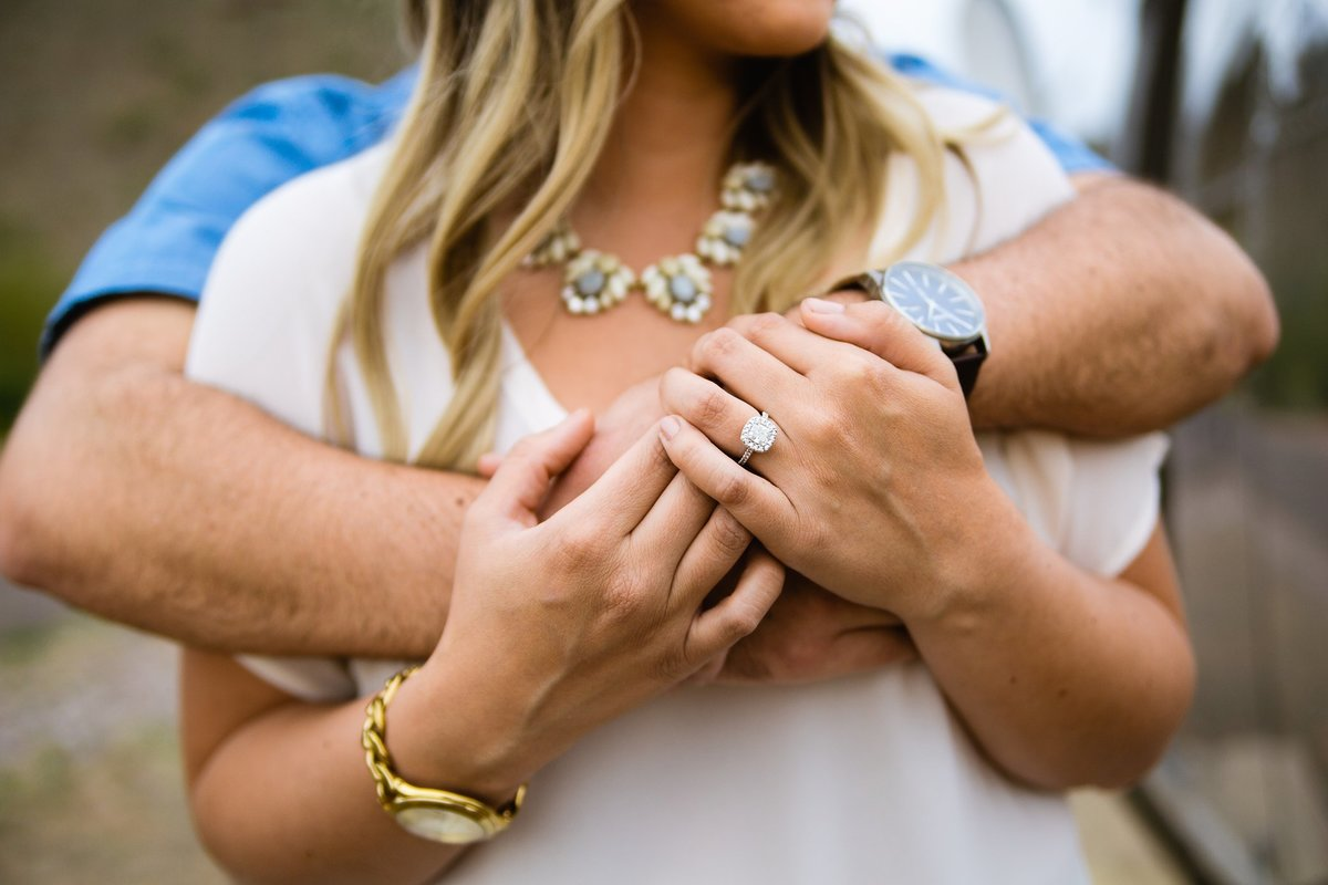 Close up image of couple holding each other showing off their engagement ring by Phoenix engagement photographer PMA Photography.